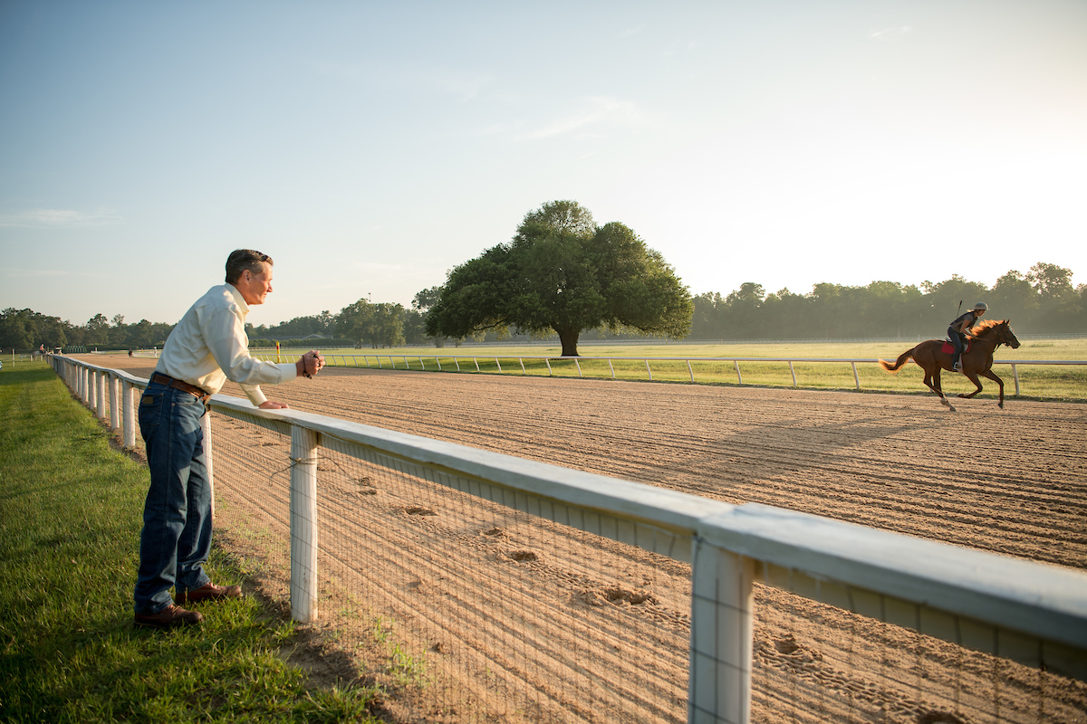 A man timing a race horse at the tracks