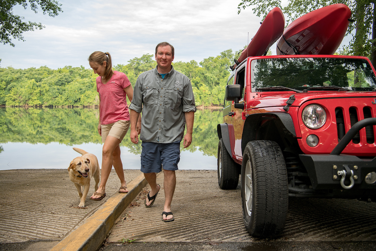 A couple with their dog, jeep, and kayaks
