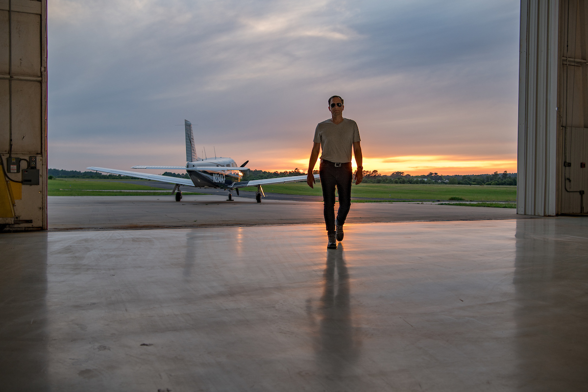 A man walking into a hangar with his plane behind him