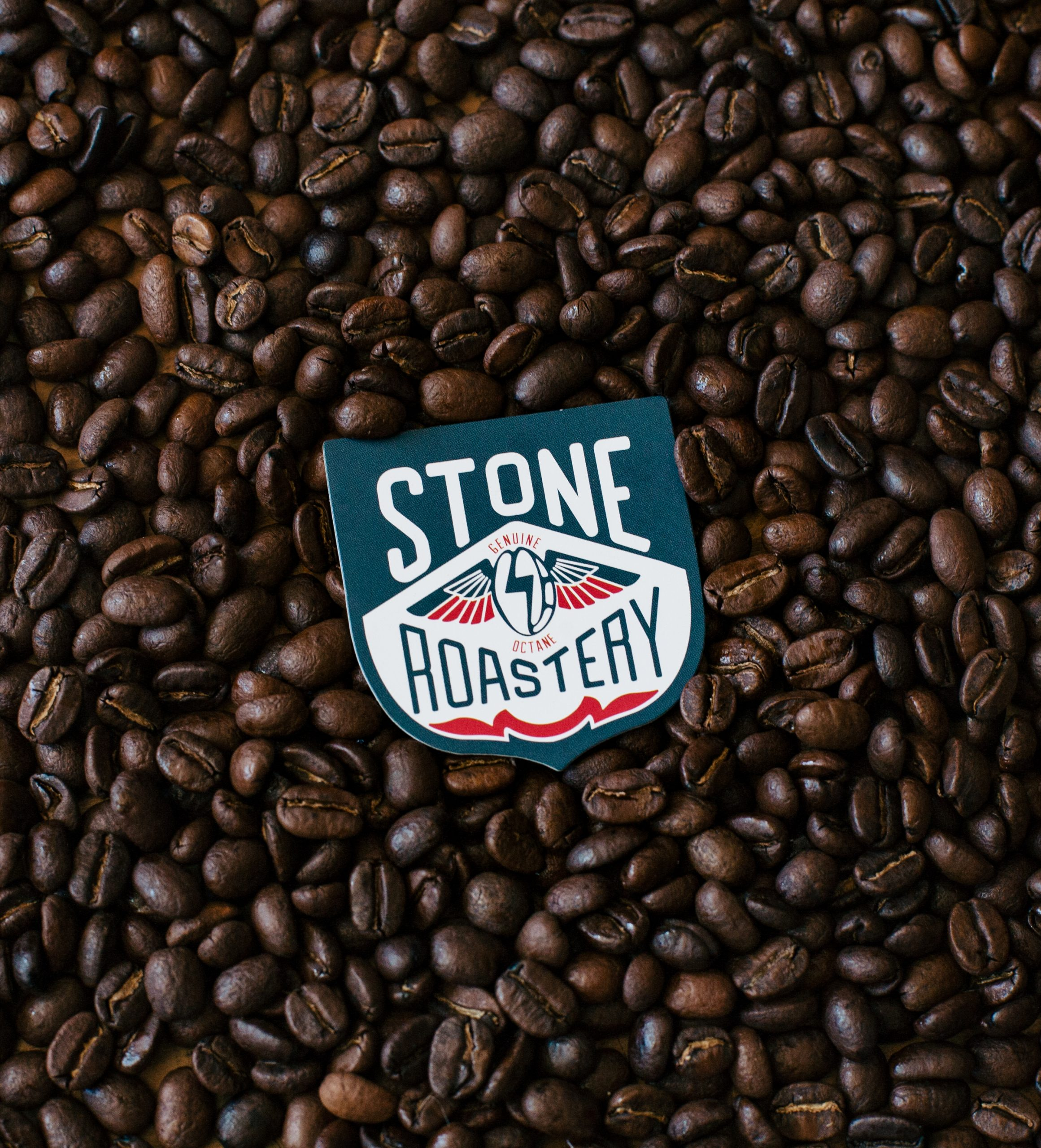Stone Roastery Logo on top of coffee beans