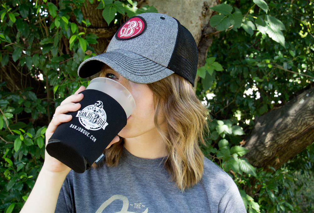 Woman drinking from a BanjoBque Koozie while wearing BanjoBque hat