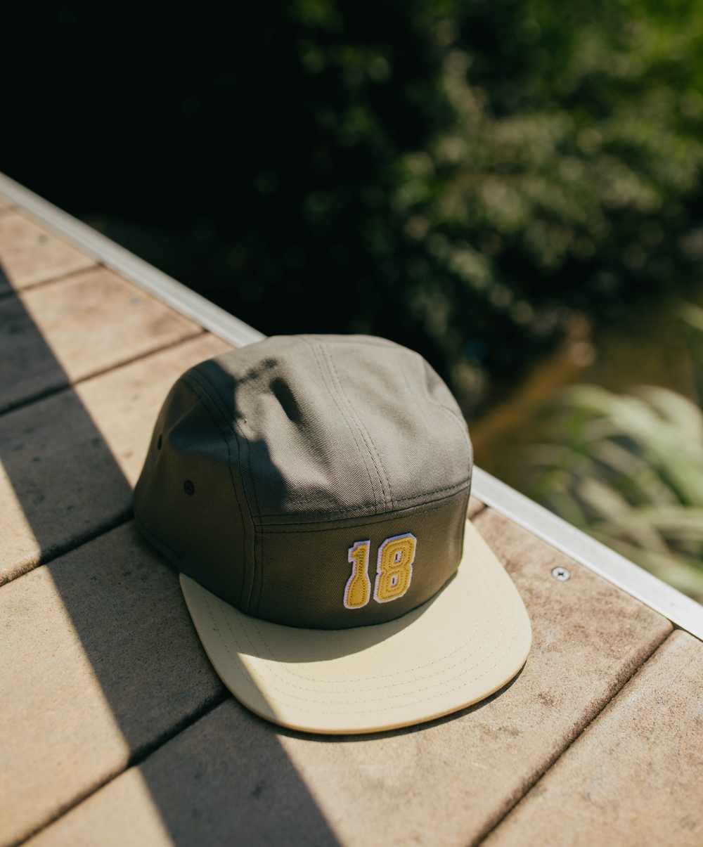 Serene 18 Five Panel Hat resting on a dock
